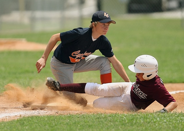 Against a background of green grass, one boy tags another boy out at the base. The boy sliding into the base wears a white batter's helmet, white pants, maroon baseball team t-shirt and maroon knee socks. The baseman tagging him looks both determined and businesslike. He has curly blond hair and wears a black baseball cap with a matching black baseball team t-shirt, grey short pants and red knee socks.